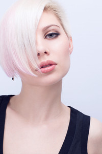 A beautiful and blond scandinavian young woman with creative hair style. Toned and natural retouched.