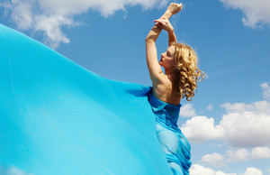 A beautiful girl wrapped in blue silk streaming in the wind