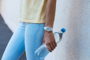 A bottle of drinking water in a female hand closeup. A woman in a yellow T-shirt and blue jeans holding a transparent bottle with water.