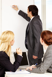 A business man drawing a plan on a whiteboard for his colleagues