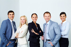A business team of five looking at camera and smiling