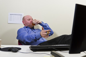 A businessman / office worker celebrating achievement with a cigar and congac at the office.