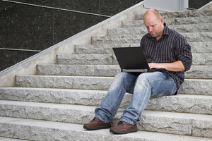 A businessman working with his computer / laptop in stairs outside. Seems focused and happy.