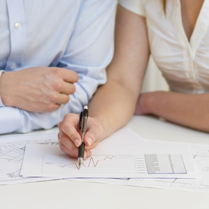 A businesswoman and a businessman in a close meeting. Pointing and looking at a printed diagram on a table.