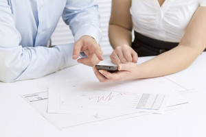 A businesswoman and a businessman in a meeting. Teamwork. Pointing and looking at a mobile phone.