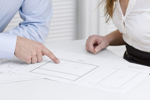 A businesswoman and a businessman in a meeting. Teamwork. Pointing and looking at a printed architect drawing on a table.