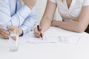 A businesswoman and a businessman in a meeting. Teamwork. Pointing and looking at a printed diagram on a table.