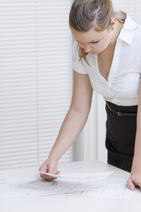 A businesswoman working. Pointing and looking at a printed paper on a table.