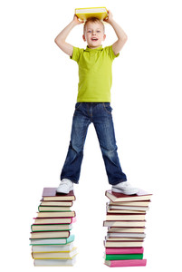 A cheerful boy with a book standing on two heaps of books