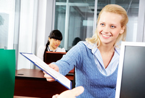 A cheerful employee giving a document to her boss