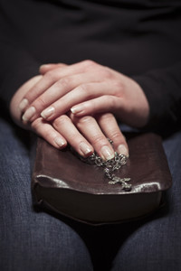A close-up of a christian woman pray. Holding a Cross over a bible.
