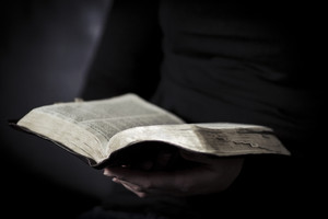 A close-up of a christian woman reading the bible. Shot with Canon 85mm 1.2L. Very shallow depth of fields.