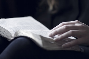 A close-up of a christian woman reading the bible. Very shallow depth of fields.