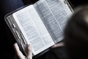 A close-up of a woman reading the bible. Very shallow depth of fields.