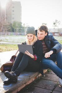 A couple of young lovers seated on sidewalk, having fun while using tablet connected internet in city back light - technology, relationship, love concept