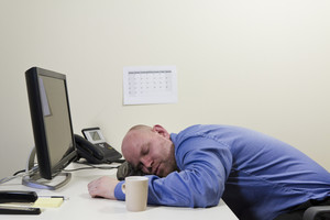 A exhausted and sleeping office worker with his head on the computer keyboard.