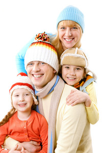 A family of four in winter clothes smiling and looking at camera