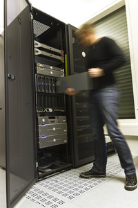 A fast working IT engineer / technician installing a server in a rack at the data center.