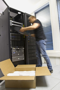 A fast working IT engineer / technician installing a server or a router in a rack at the data center.