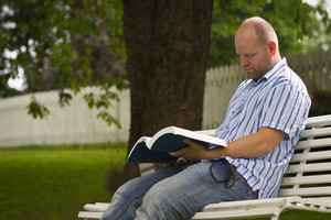 A focused man reading / studying a book in a park. Sitting on a bench with a book and a laptop.