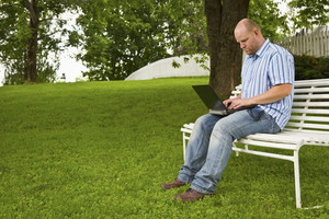 A focused man working / studying a book in a park. Sitting on a bench with a book and a laptop.