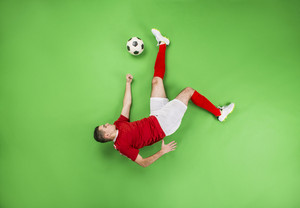 A football player with a ball in action. Studio shot on a green backroung.