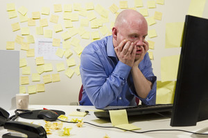 A frustrated office worker looking at his computer monitor.