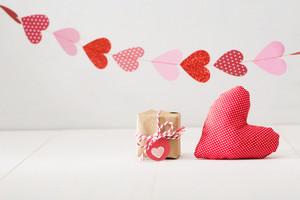 A garland of hearts above a small gift-wrapped box and red textile heart on a neutral off white background with copyspace - Valentines Day greeting card background