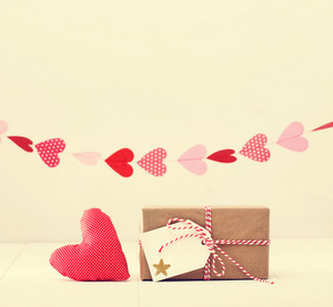 A garland of hearts above a small gift-wrapped box and red textile heart on a neutral white background with copyspace