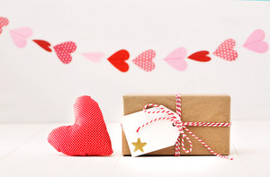 A garland of hearts above a small gift-wrapped box and red textile heart on a neutral white background