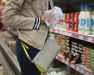 A girl in a beige jacket, blue jeans and with women's bag buy dairy products at the supermarket. In her hands a bag of food. In the background you can see the showcase of dairy products.
