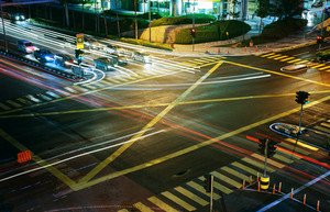 A high angle view of  treet intersection, with yellow cross walk markings, traffic signal lights, and curb cuts.