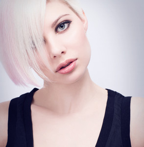 A high key photo of a beautiful and glamorous young woman with creative hair style. Colored and natural retouched.
