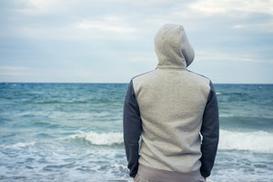 A man stands on the beach in a tracksuit with a hood and looking at the sea. Cloudy weather, rear view.