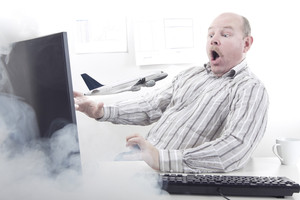 A Plane flying out of a Office workers computer monitor. Order vacation / holiday / plane tickets on internet.