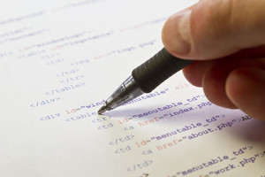 A programmer / man pointing with his pen at HTML code for a web page