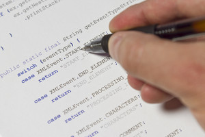 A programmer / man pointing with his pen at Java computer code. Software / application program code. XML parser.