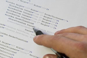 A programmer / man pointing with his pen at software computer code. Software / application program code. XML parser.