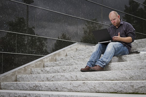 A questioning and frustrated man working with his computer / laptop in stairs outside.