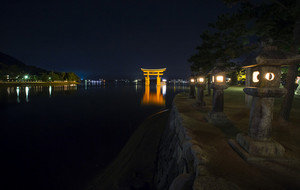 A ship passing under the famous orange shinto gate (Torii) of Miyajima island of Hiroshima prefecture, Japan at night