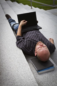 A sleeping / resting / exhausted man working with his computer / laptop in stairs outside.