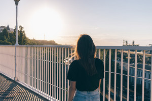 A slender brunette girl is walking along the bridge in summer during sunset, view from the back