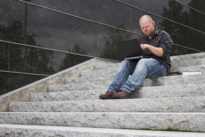 A student / businessman try to find a solution on his computer / laptop in stairs outside.