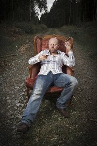 A thoughtful man / guy drinking cognac and smoke cigar in a vintage chair in the middle of a road in woods.