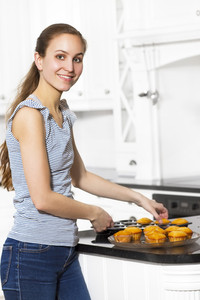 A woman baking muffins in white kitchen.