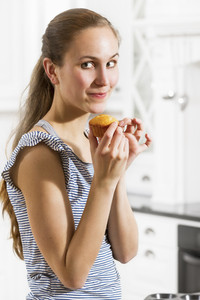 A woman eating a muffins.