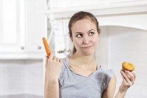 A woman has to choose between a muffins and a carrot. Diet consept.