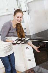 A woman making / baking muffins in white kitchen modern kitchen.