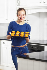 A woman making muffins in white kitchen.