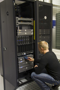 A working IT engineer / technician insert a backup tape in a backup robot in rack. Shot in a data center.